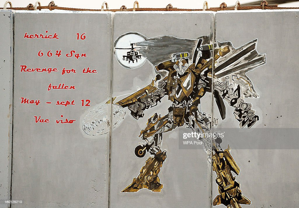 In this previously unissued image released on January 27 a hand painted mural from 664 Squadron is seen on a prefabricated blast wall between Apache...