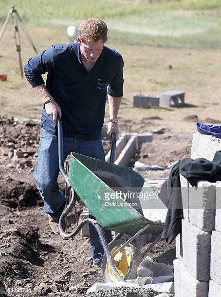 In this previously unreleased photo Prince Harry helps lay the foundations for the new Sentebale Mateanong Herd Boy School during a visit to the site...