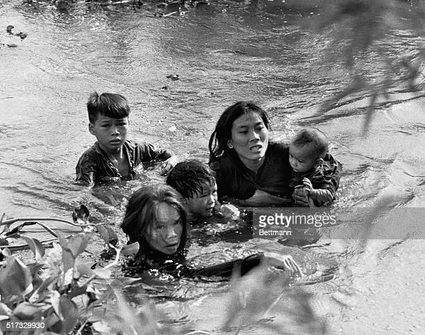 In this Pulitzer Prize winning photo A Vietnamese mother and her children wade across a river fleeing a bombing raid on Qui Nhon by United States...
