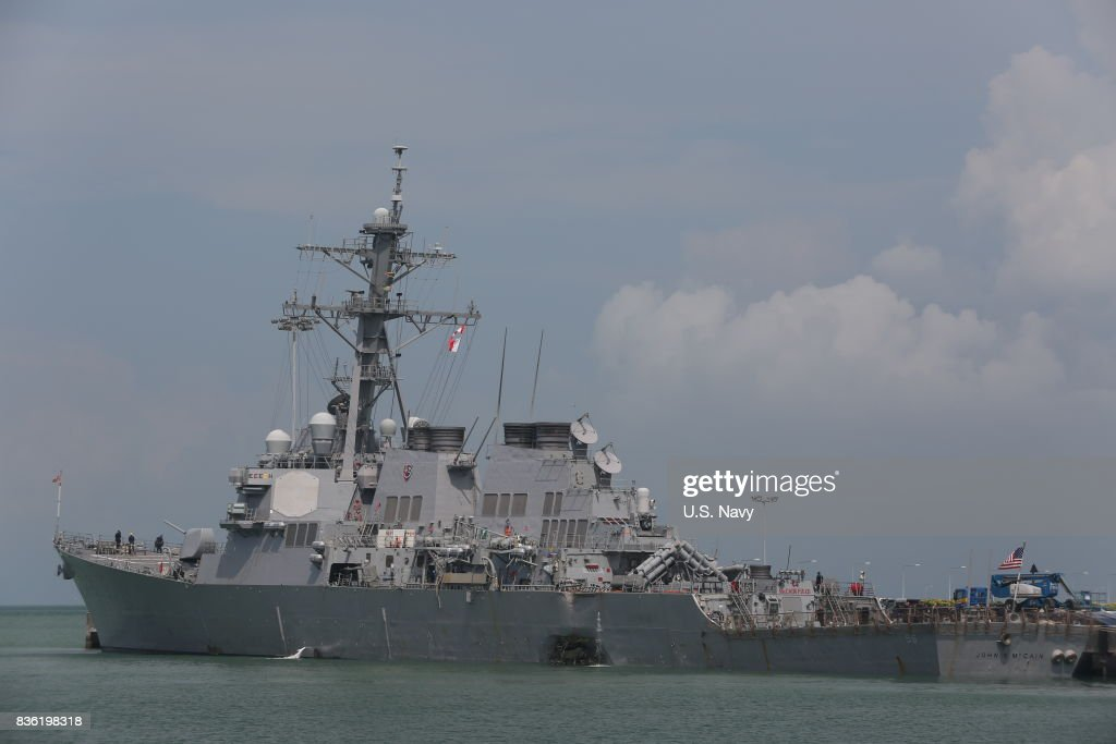In this released U.S. Navy handout, guided-missile destroyer USS John S. McCain (DDG 56) moored pier side at Changi Naval Base, Republic of Singapore following a collision with the merchant vessel Alnic MC while underway east of the Straits of Malacca and Singapore on Aug. 21. Significant damage to the hull resulted in flooding to nearby compartments, including crew berthing, machinery, and communications rooms. Damage control efforts by the crew halted further flooding. The incident will be investigated.