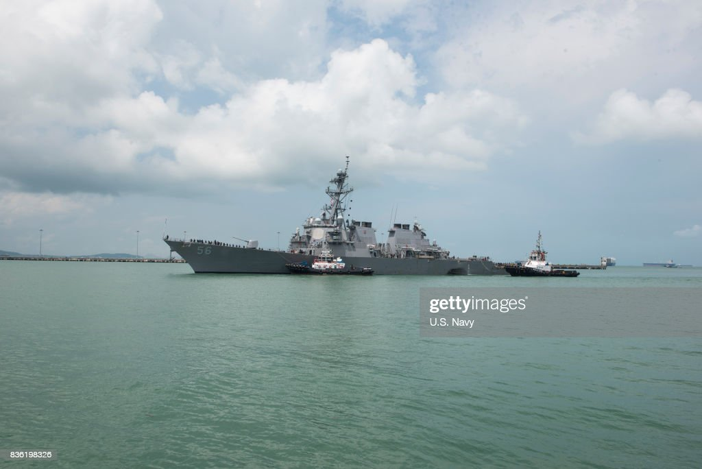 In this released U.S. Navy handout, tugboats from Singapore assist the Guided-missile destroyer USS John S. McCain (DDG 56) at it steers towards Changi Naval Base, Republic of Singapore following a collision with the merchant vessel Alnic MC while underway east of the Straits of Malacca and Singapore on Aug. 21. Significant damage to the hull resulted in flooding to nearby compartments, including crew berthing, machinery, and communications rooms. Damage control efforts by the crew halted further flooding. The incident will be investigated.