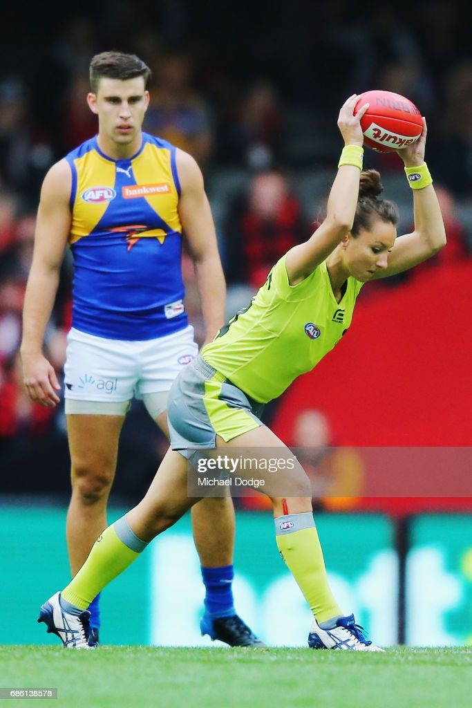 In this series Umpire Ellen Glouftsis, making her debut as the first ever women to umpire an AFL match, takes her first bounce of the ball during the round nine AFL match between the Essendon Bombers and the West Coast Eagles at Etihad Stadium on May 21, 2017 in Melbourne, Australia.