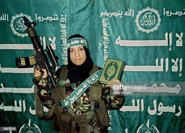 In this undated handout image Reem Slaleh Raiyshi a mother of two children from Gaza stands holding a weapon and the Quran holy book Raiyshi was...