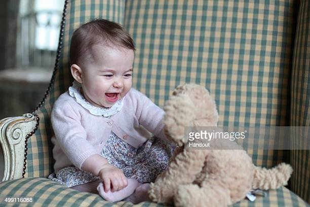 In this undated handout photo provided by HRH The Duchess of Cambridge Princess Charlotte of Cambridge plays with a teddy as she is seen at Anmer...