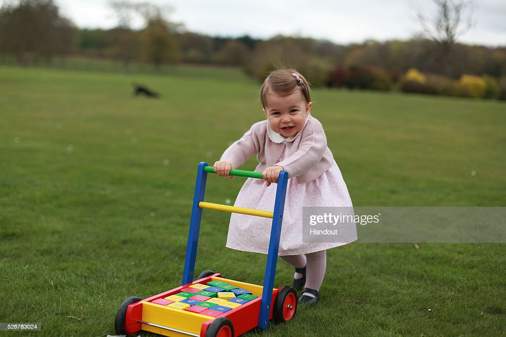 In this undated handout photo provided by HRH The Duke and Duchess of Cambridge released on May 1, 2016, Princess Charlotte of Cambridge looks on as she walks while pushing her toy blocks across the lawn outside as her mother Catherine, Duchess of Cambridge takes her photo ahead of her first birthday on May 2, 2016 at Anmer Hall on April 2016 in Norfolk, England. The young Princess will celebrate her first birthday on May 2. (Photo by HRH The Duchess of Cambridge via Getty mages) EDITORIAL USE ONLY. NO COMMERCIAL USE (including any use in merchandising, advertising or any other non-editorial use including, for example, calendars, books and supplements). This photograph is provided to you strictly on condition that you will make no charge for the supply, release or publication of it and that these conditions and restrictions will apply (and that you will pass these on) to any organisation to whom you supply it. All other requests for use should be directed to the Press Office at Kensington Palace in writing.