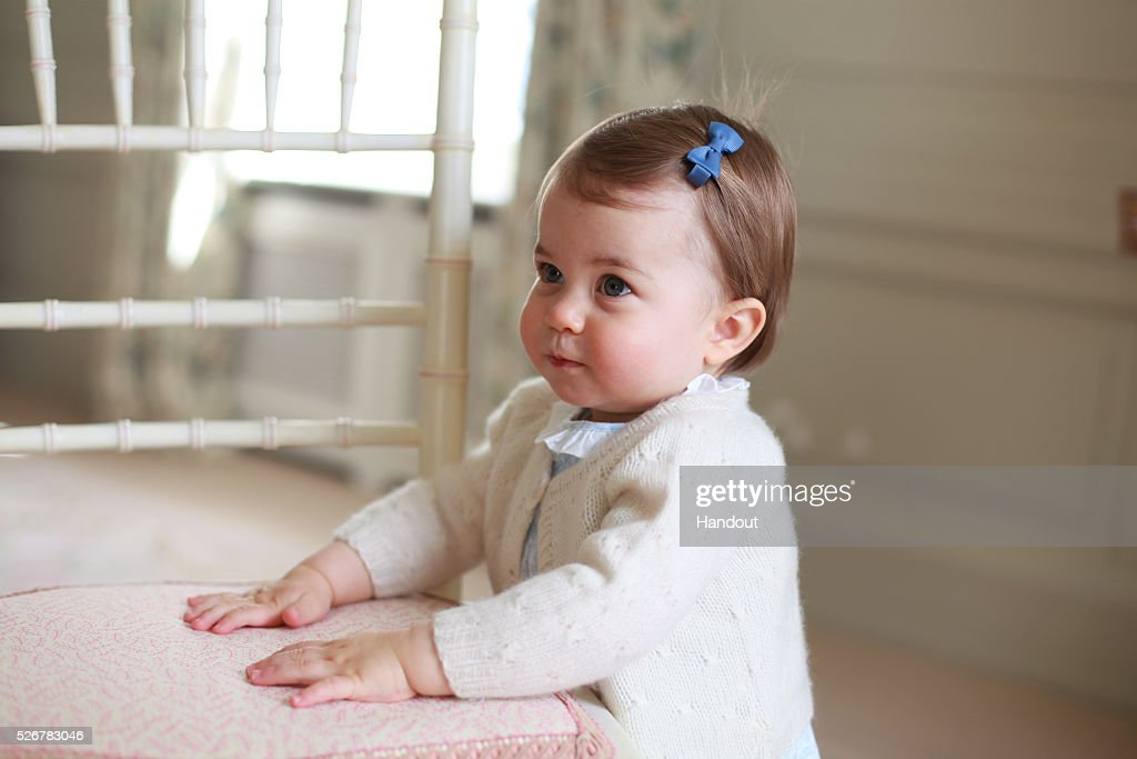 In this undated handout photo provided by HRH The Duke and Duchess of Cambridge released on May 1, 2016, Princess Charlotte of Cambridge looks up with her hands placed on a chair as her mother Catherine, Duchess of Cambridge takes her photo ahead of her first birthday on May 2, 2016 at Anmer Hall on April 2016 in Norfolk, England. The young Princess will celebrate her first birthday on May 2. (Photo by HRH The Duchess of Cambridge via Getty mages) EDITORIAL USE ONLY. NO COMMERCIAL USE (including any use in merchandising, advertising or any other non-editorial use including, for example, calendars, books and supplements). This photograph is provided to you strictly on condition that you will make no charge for the supply, release or publication of it and that these conditions and restrictions will apply (and that you will pass these on) to any organisation to whom you supply it. All other requests for use should be directed to the Press Office at Kensington Palace in writing.