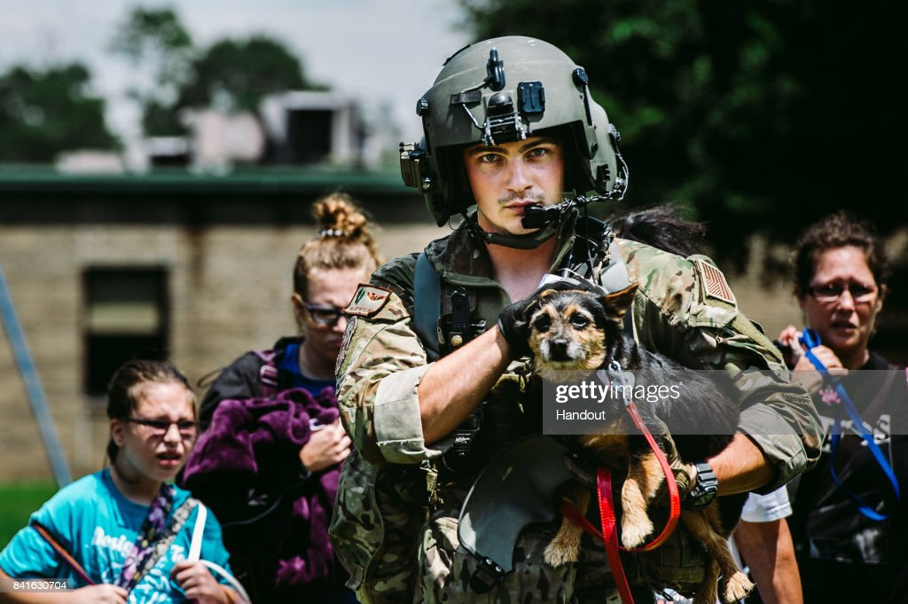 In this U.S. Air Force handout, Senior Airman Austin Hellweg, 129th Rescue Squadron special missions aviator, carries a dog and leads a family into an HH-60 Pavehawk for extraction to a safer location during the relief effort for Hurricane Harvey, Aug. 31st, 2017, Beaumont, Texas. The relief efforts have a conglomerate of active, guard and reserve units from all branches aiding the federal government to help Texas recover from Hurricane Harvey.