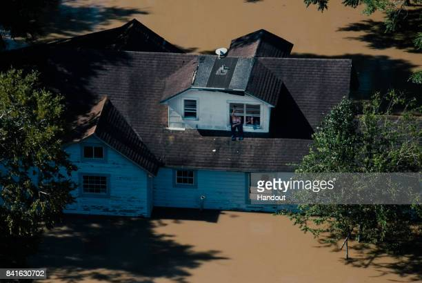 In this US Air Force handout Two residents of Texas flooded into their home wave out their window signaling they are ok during an HH60 flyover Aug...