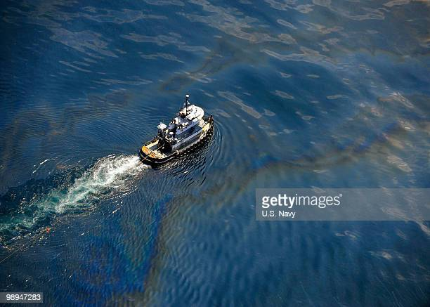 In this US Navy handout A tug boat moves through the oil slick May 6 2010 in the Gulf of Mexico The US Coast Guard is overseeing oil burns after the...