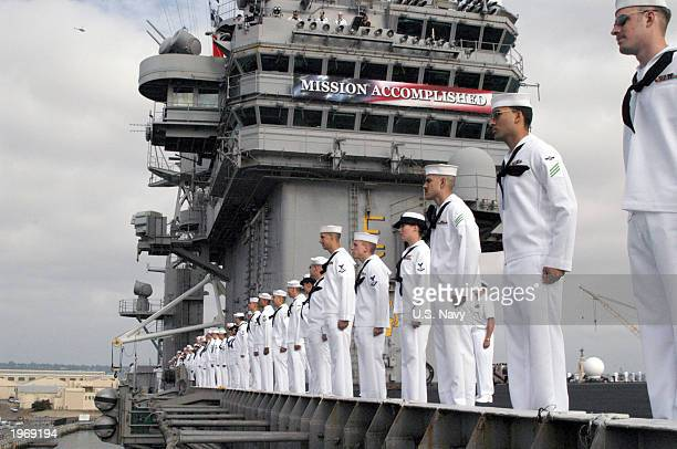 In this US Navy handout photo Sailors aboard USS Abraham Lincoln man the rail as they arrive at Naval Air Station North Island to a cheering crowd of...