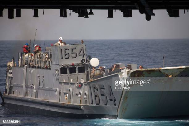 In this US Navy handout US Marines assigned to the 26th Marine Expeditionary Unit and US Navy Sailors assigned to Expeditionary Strike Group 2 depart...