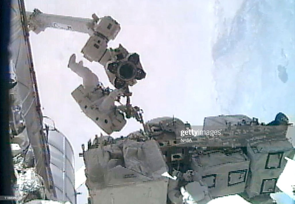 In this video screen grab provided by the National Aeronautics and Space Administration (NASA), NASA astronaut Ronald Garan i(L) installs a foot restraint on the Canada Arm 2 as he and astronaut Michael Fossum (btm R) do repairs on the International Space Station during a planned six-and-a-half-hour spacewalk July 12, 2011 in space. Space shuttle Atlantis has embarked on a 12-day mission to the International Space Station where it will deliver the Raffaello multi-purpose logistics module packed with supplies and spare parts. This will be the final launch of the space shuttle program, which began on April 12, 1981 with the launch of Colombia.