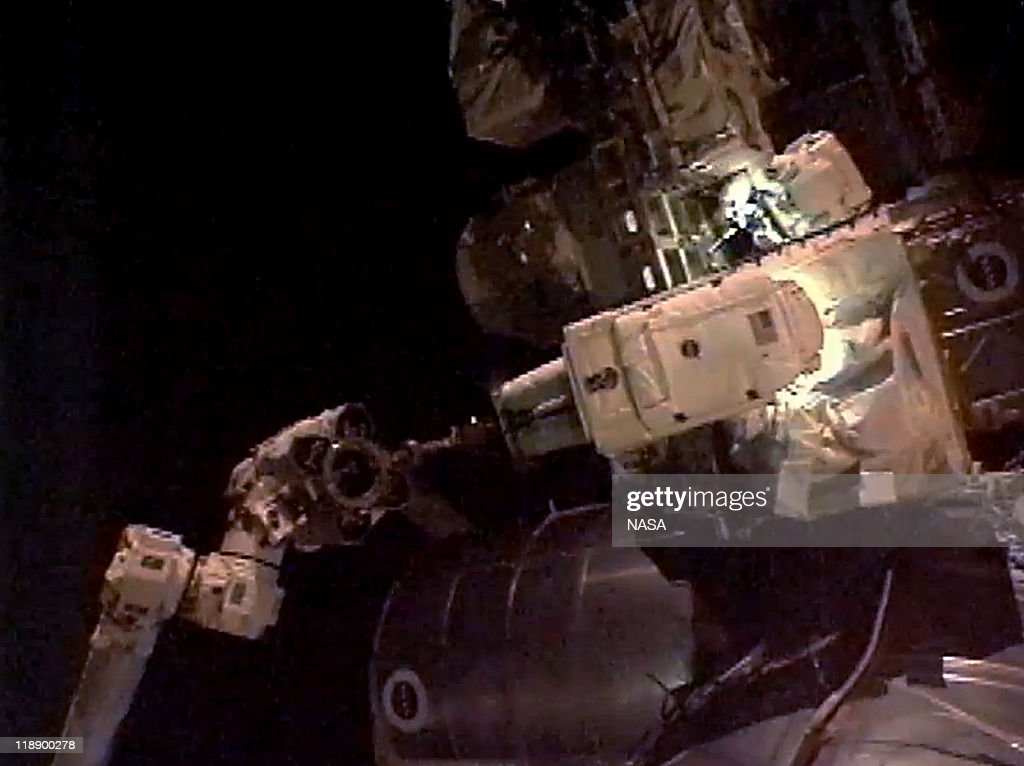 In this video screen grab provided by the National Aeronautics and Space Administration (NASA), NASA astronaut Ronald Garan on the Canada Arm 2 and astronaut Michael Fossum (top) do work to remove a failed ammonia pump module from a storage platform on the International Space Station during a planned six-and-a-half-hour spacewalk July 12, 2011 in space. This is the 160th spacewalk devoted to station assembly and maintenance since construction began in 1998. Space shuttle Atlantis has embarked on a 12-day mission to the International Space Station where it will deliver the Raffaello multi-purpose logistics module packed with supplies and spare parts. This will be the final launch of the space shuttle program, which began on April 12, 1981 with the launch of Colombia.