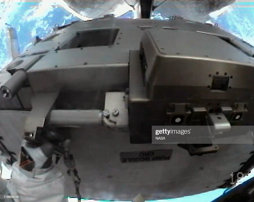 In this video screen grab provided by the National Aeronautics and Space Administration (NASA), seen from the helmet camera of NASA astronaut Ronald Garan, attached to the Canada Arm 2 he moves a failed ammonia pump module from a storage platform on the International Space Station to the cargo bay of the space shuttle Atlantis during a planned six-and-a-half-hour spacewalk July 12, 2011 in space. This is the 160th spacewalk devoted to station assembly and maintenance since construction began in 1998. Space shuttle Atlantis has embarked on a 12-day mission to the International Space Station where it will deliver the Raffaello multi-purpose logistics module packed with supplies and spare parts. This will be the final launch of the space shuttle program, which began on April 12, 1981 with the launch of Colombia.