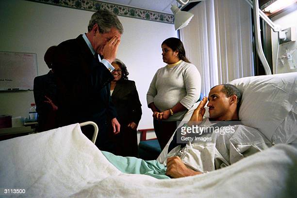 In this White House handout US President George W Bush salutes US Army Staff Sergeant Santiago Frias of Bronx NY after giving him the purple heart at...