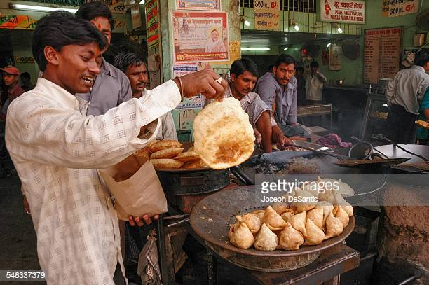 In Varanasi India a man holds a hot Bhatoora fried bread in front of cooking samosas a fried pastry with savory filling