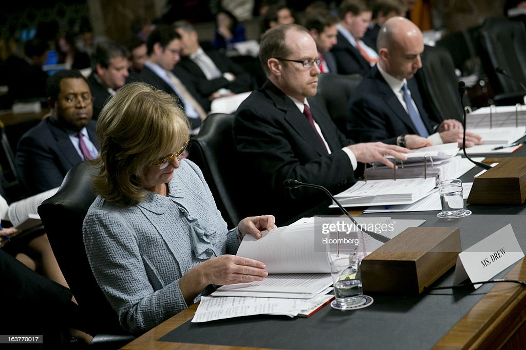 Ina Drew, former chief investment officer with JPMorgan Chase & Co., left to right, Peter 'Pete' Weiland, former head of market risk for the chief investment office at JPMorgan Chase, and Ashley Bacon, acting chief risk officer with JPMorgan Chase, look through an exhibits folder during a Senate Permanent Subcommittee on Investigations hearing in Washington, D.C., U.S., on Friday, March 15, 2013. JPMorgan Chase, the biggest U.S. bank by assets, compensated chief investment office traders in a way that encouraged risk-taking before the unit amassed losses exceeding $6.2 billion, a Senate committee said. Photographer: Andrew Harrer/Bloomberg via Getty Images