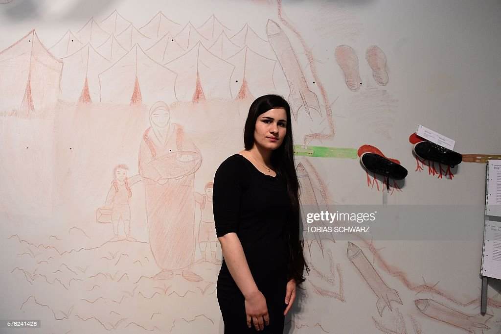 Ina Sado refugee from Iraq poses next to her exhibits during a preview of the show 'daHEIM glances into fugitive lives' on July 21 2016 at the Museum...