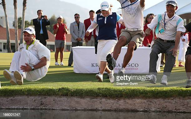 Inbee Park of South Korea and her entourage take the traditional jump into Poppy's Pond following her victory in the final round of the Kraft Nabisco...