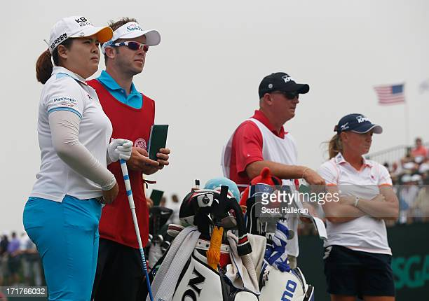 Inbee Park of South Korea and Stacy Lewis wait with their caddies on the first tee during the second round of the 2013 US Women's Open at Sebonack...