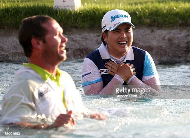 Inbee Park of South Korea high laughs with her caddie Brad Beecher after taking the traditional jump into Poppy's Pond following her victory in the...