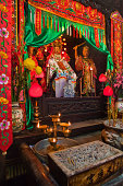 Incense candles and statues at altar