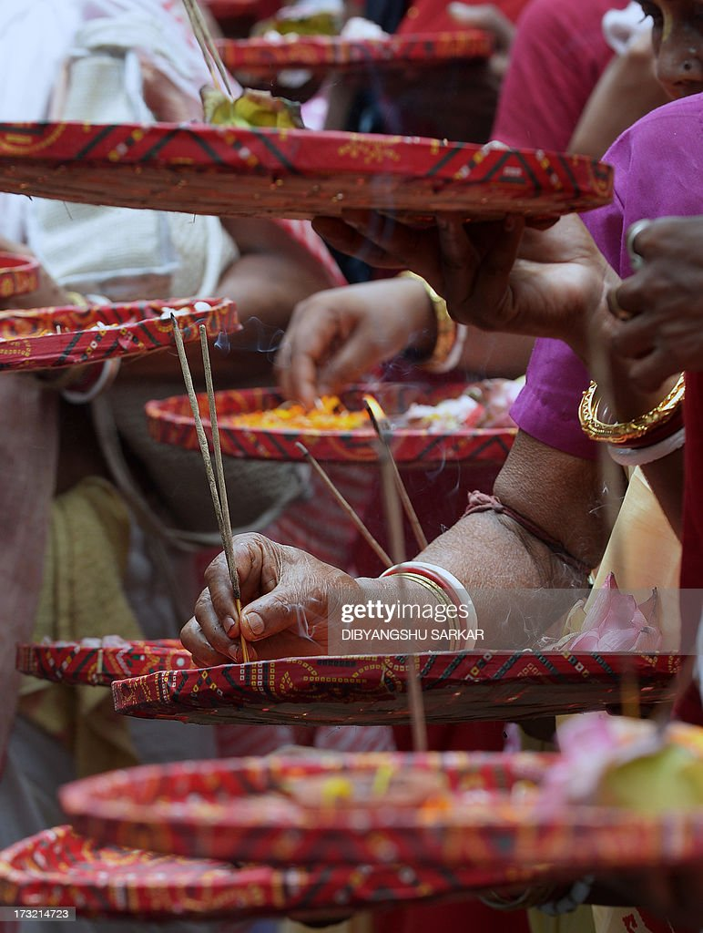 Incense sticks burn as Indian Hindu pilgrims and devotees of the International Society of Krishna Conciousness (ISKON) wait to pull the holy rope of the Chariot of Lord Jagannath during the Rath Yatra celebration in Kolkata on July 10, 2013. According to mythology, the Ratha Yatra dates back some 5,000 years when Hindu god Krishna, along with his older brother Balaram and sister Subhadra, were pulled on a chariot from Kurukshetra to Vrindavana by Krishna's devotees. AFP PHOTO/Dibyangshu SARKAR