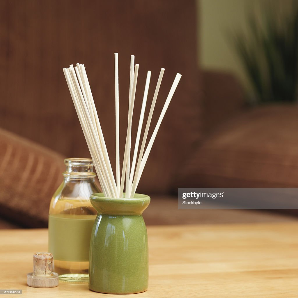 Incense sticks in a burner with bottle of oil : Stock Photo
