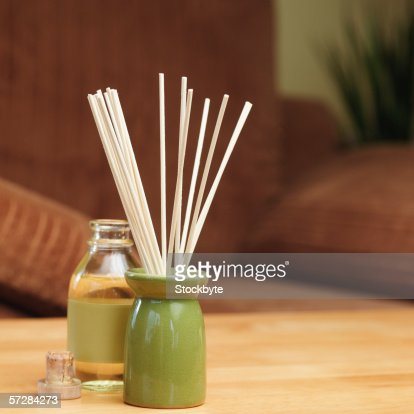 Incense sticks in a burner with bottle of oil : Photo