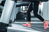 Woman using incline threadmill in modern gym. Incline threadmills are used to simulate uphill walking or running and deliver additional workout benefits to users. Woman is wearing black yoga pants and