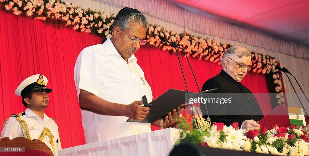 Incoming Chief Minister of the southern Indian state of Kerala Pinarayi Vijayan (C) stands alongside Governor of Kerala P. Sathasivam(R)as he takes part in a swearing-in ceremony in Thiruvananthapuram on May 25, 2016. / AFP / STR