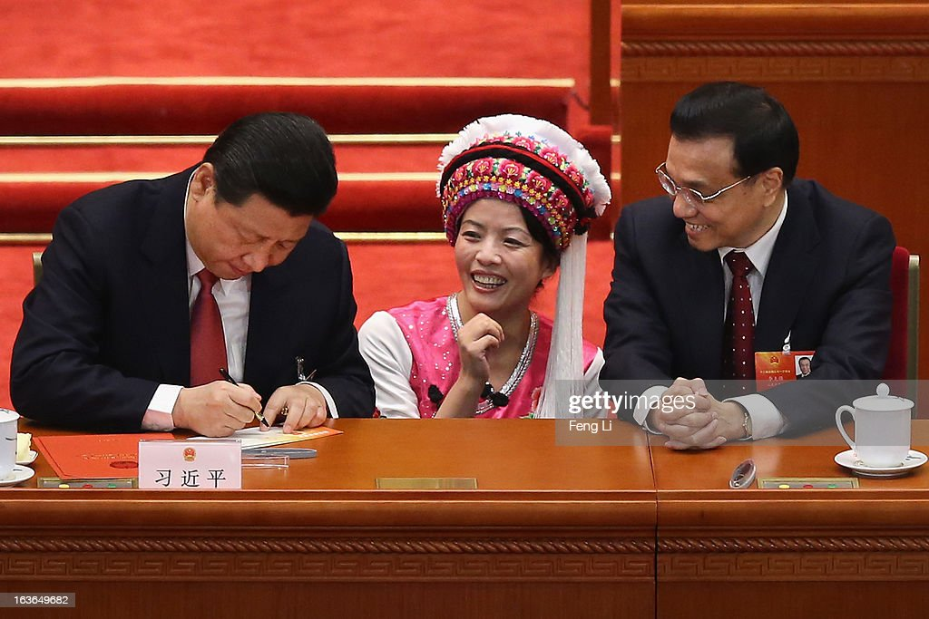 Incoming Chinese President Xi Jinping (left) and Vice Premier Li Keqiang (R) sign an autograph for an Ethnic minority delegate during the fourth plenary meeting of the National People's Congress at the Great Hall of the People on March 14, 2013 in Beijing, China. Xi Jinping, general secretary of the Communist Party of China Central Committee, was elected President of the People's Republic of China and Chairman of the Central Military Commission on Thursday.