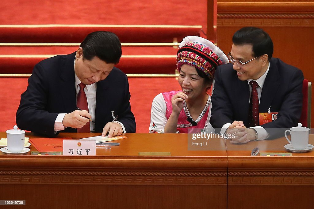 Incoming Chinese President <a gi-track='captionPersonalityLinkClicked' href=/galleries/search?phrase=Xi+Jinping&family=editorial&specificpeople=2598986 ng-click='$event.stopPropagation()'>Xi Jinping</a> (left) and Vice Premier <a gi-track='captionPersonalityLinkClicked' href=/galleries/search?phrase=Li+Keqiang&family=editorial&specificpeople=2481781 ng-click='$event.stopPropagation()'>Li Keqiang</a> (R) sign an autograph for an Ethnic minority delegate during the fourth plenary meeting of the National People's Congress at the Great Hall of the People on March 14, 2013 in Beijing, China. <a gi-track='captionPersonalityLinkClicked' href=/galleries/search?phrase=Xi+Jinping&family=editorial&specificpeople=2598986 ng-click='$event.stopPropagation()'>Xi Jinping</a>, general secretary of the Communist Party of China Central Committee, was elected President of the People's Republic of China and Chairman of the Central Military Commission on Thursday.