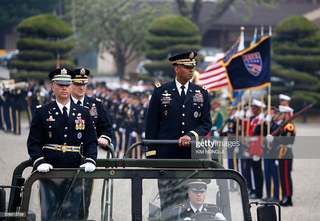 Incoming Commander General Vincent K. Brooks (R) and outgoing Commander General Curtis M. Scaparrotti (2nd L) inspect honor guards during a change of command ceremony for the United Nations Command, Combined Forces Command, and United States Forces Korea at the US military base in Seoul on April 30, 2016. / AFP / pool / KIM