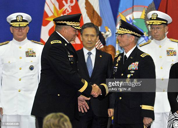 Incoming General James Thurman shakes hands with outgoing General Walter Sharp as Admiral Mike Mullen chairman of the US Joint Chiefs of Staff...