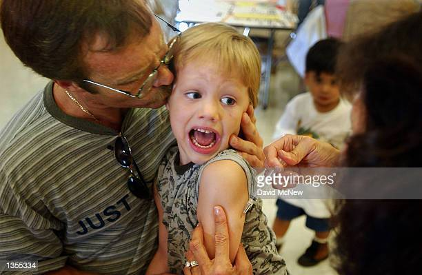 Incoming kindergartener Jeremy Conner reacts to a Measles Mumps and Rubella vaccination as his father Mark Conner tries to comfort him August 26 2002...