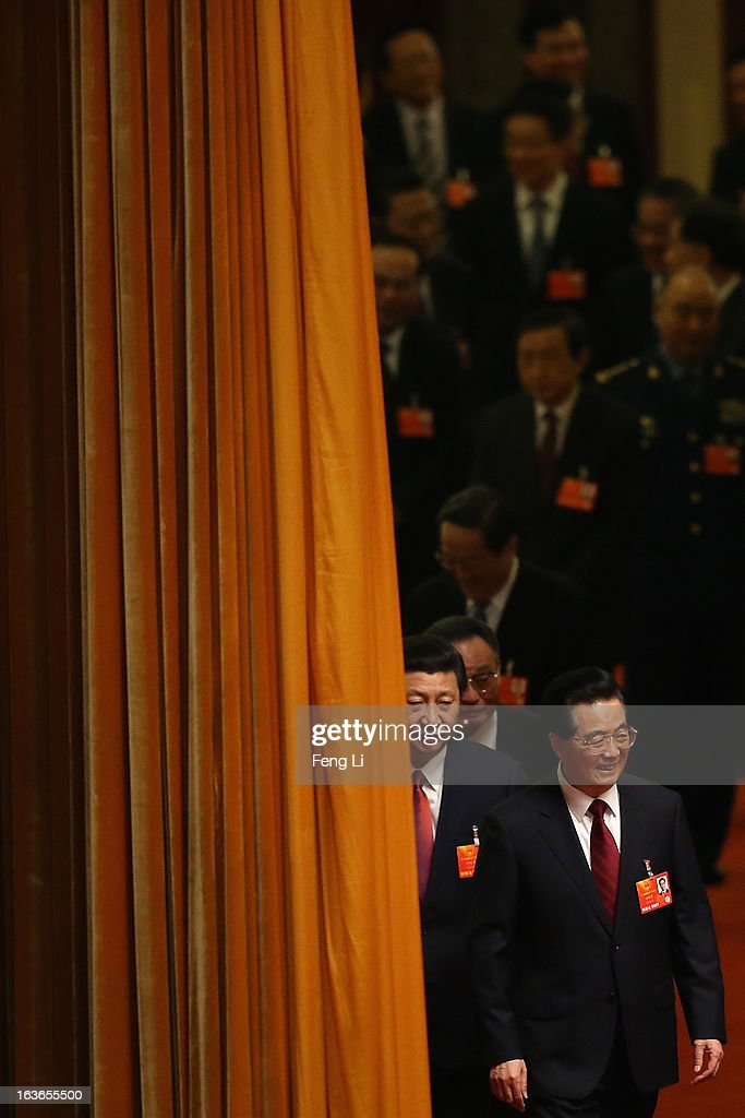 Incoming President Xi Jinping follows behind the outgoing Chinese President Hu Jintao (Front) to attend the fourth plenary meeting of the National People's Congress at the Great Hall of the People on March 14, 2013 in Beijing, China. Xi Jinping, general secretary of the Communist Party of China Central Committee, was elected President of the People's Republic of China and Chairman of the Central Military Commission on Thursday.