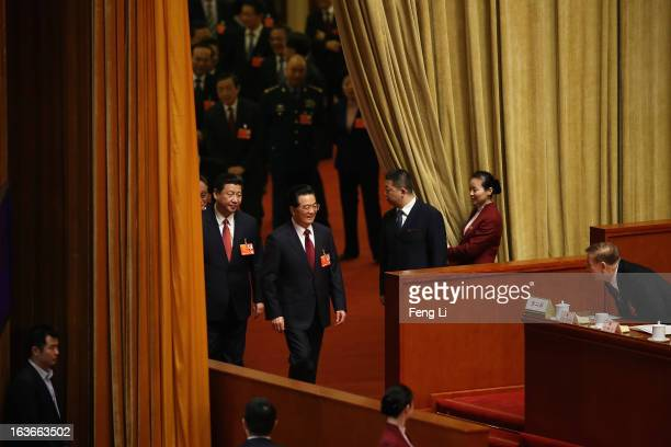 Incoming President Xi Jinping follows behind the outgoing Chinese President Hu Jintao to attend the fourth plenary meeting of the National People's...