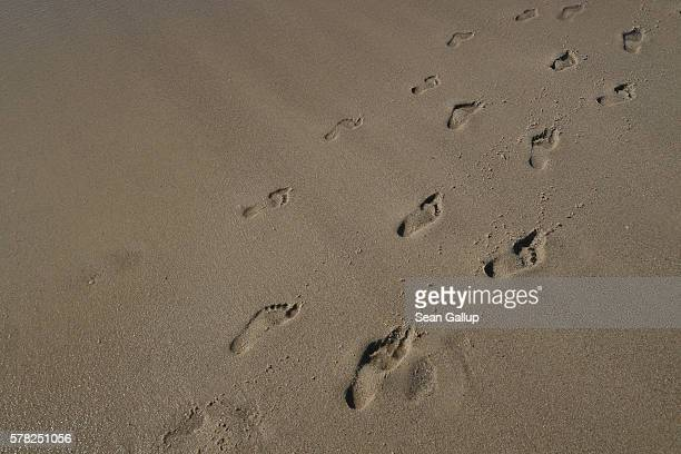 Incoming waves wash away footprints left by visitors in the sand along a beach on Sylt Island on July 19 2016 near Wenningstedt Germany Sylt Island...