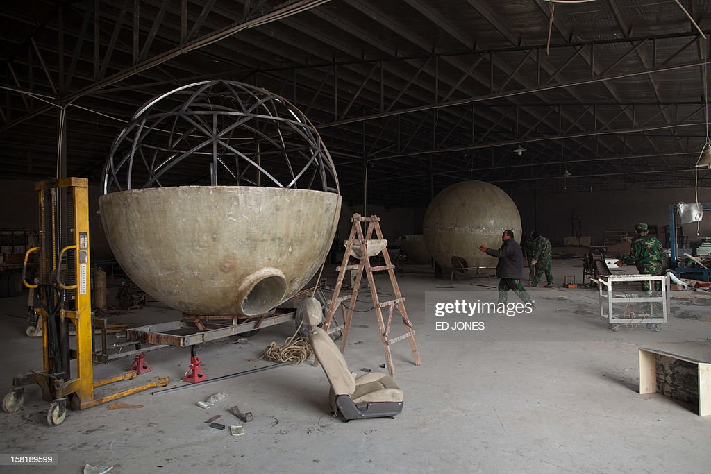 Incomplete survival pods stand in the workshop of farmer Liu Qiyuan which he has also dubbed 'Noah's Arc', in a yard at his home in the village of Qiantun, Hebei province, south of Beijing on December 11, 2012. Inspired by the apocalyptic Hollywood movie '2012' and the 2004 Asian tsunami, Liu hopes that his creations consisting of a fibreglass shell around a steel frame will be adopted by government departments and international organisations for use in the event of tsunamis and earthquakes. Liu has built seven pods which are able to float on water, some of which have their own propulsion. The airtight spheres with varying interiors contain oxygen tanks and seatbelts with space for around 14 people, and are designed to remain upright when in water. AFP PHOTO / Ed Jones