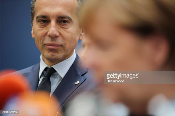 Incumbent Austrian Chancellor Christian Kern looks on as German Chancellor Angela Merkel speaks to the media ahead of a European Council Meeting at...