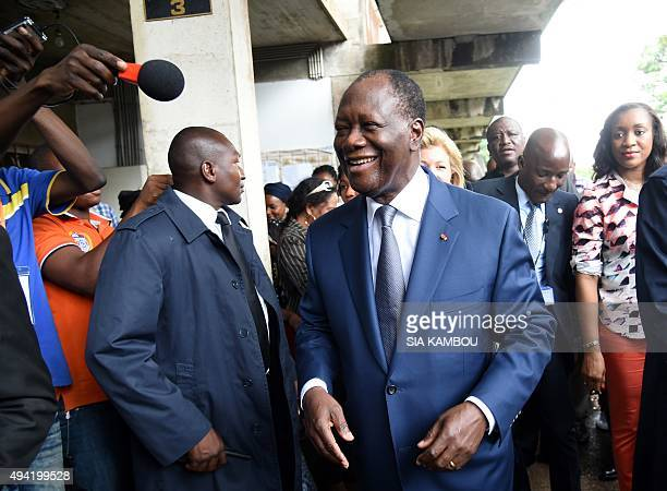 Incumbent Ivory Coast president Alassane Ouattara smiles to supporters as he leaves a polling station after voting in the Cocody residential district...