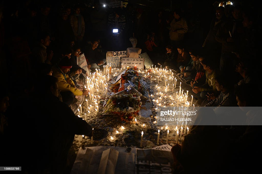 Indain protestors light candles around a mannequin representing the rape victim during a rally in New Delhi on December 31,2012. The family of an Indian gang-rape victim said they would not rest until her killers are hanged as they spoke of their own pain and trauma over a crime that has united the country in grief AFP PHOTO/ SAJJAD HUSSAIN