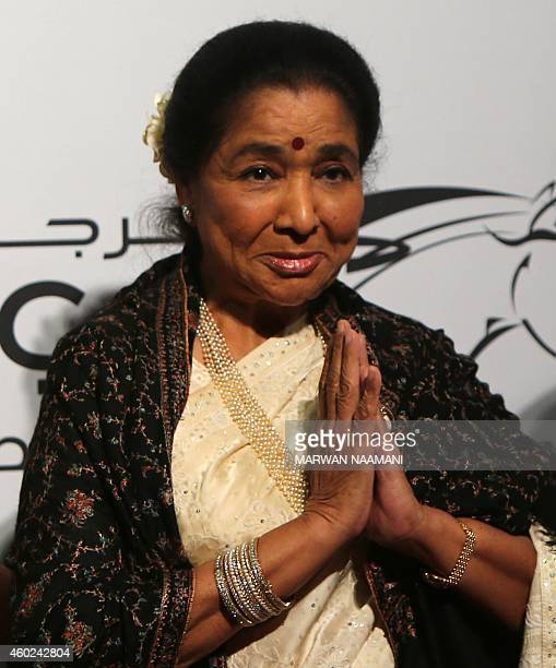 Indain singer Asha Bhosle best known as a playback singer in Hindi cinema poses for photographers as she arrives to the opening session of the 11th...