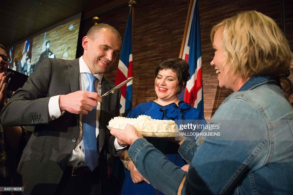 Independant presidential candidate Gudni Johannesson (L) cuts a cake next to his wife Eliza Reid at an election party in Reykjavik, on June 25, 2016. Political newcomer Gudni Johannesson claimed victory in Iceland's presidential election after riding a wave of anti-establishment sentiment, though the vote was eclipsed by the country's eagerly-anticipated and historic Euro football match. / AFP / HALLDOR