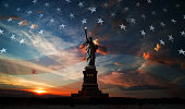 Statue of Liberty on the background of flag usa and sunrise