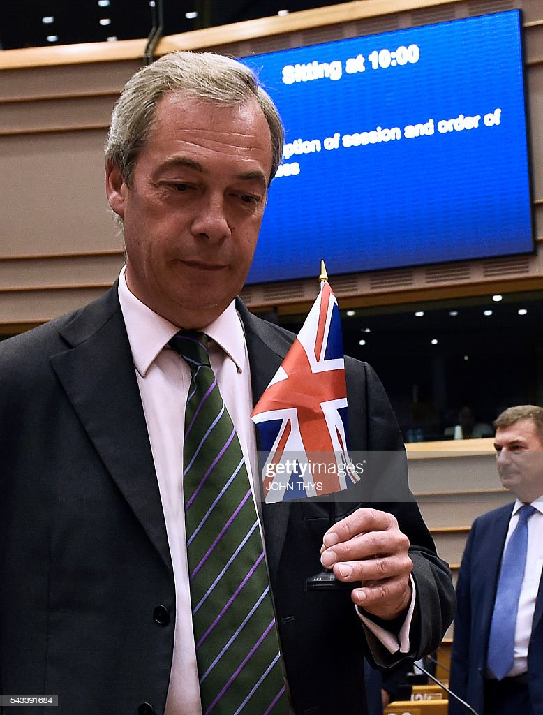 UK Independence Party (UKIP) leader Nigel Farage holds a British flag as he arrives for a plenary sessionat the EU headquarters in Brussels on June 28, 2016. European Commission chief Jean-Claude Juncker called on June 28 on Prime Minister David Cameron to clarify quickly when Britain intends to leave the EU, saying there can be no negotiation on future ties before London formally applies to exit. / AFP / JOHN