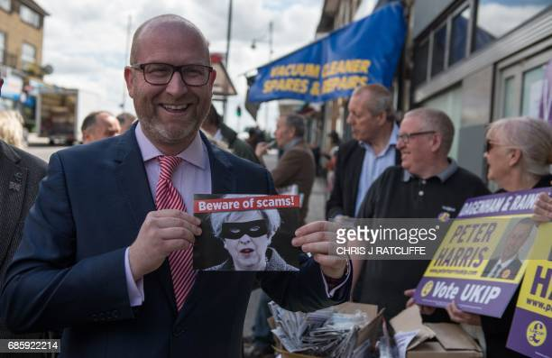UK Independence Party leader Paul Nuttall reacts as he poses with a poster depicting Britain's Prime Minister Theresa May as he campaigns the party's...