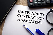 Independent contractor agreement, pen, glasses and calculator on desk