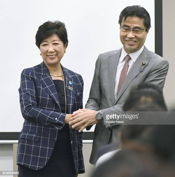 Independent House of Representatives lawmaker Masaru Wakasa shakes hands with his close ally Tokyo Gov Yuriko Koike at his political academy in Tokyo...